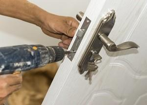 A residential locksmith working on a lock in Phoenix, AZ